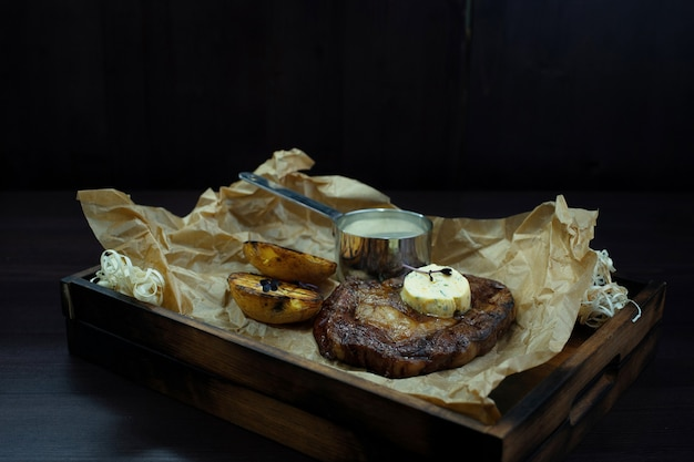 Steak juteux grillé avec du beurre et des tranches d'aubergines cuites au four sur une planche vintage se dresse sur une table en bois