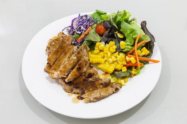Steak et légumes sur une assiette blanche et sur une table en verre