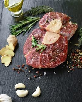 Steak osso buco cru sur une pierre noire entourée d'épices