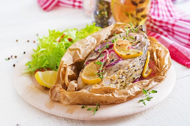 Steak de poisson blanc (carpe) cuit dans du papier sulfurisé avec des légumes. plat de poisson.