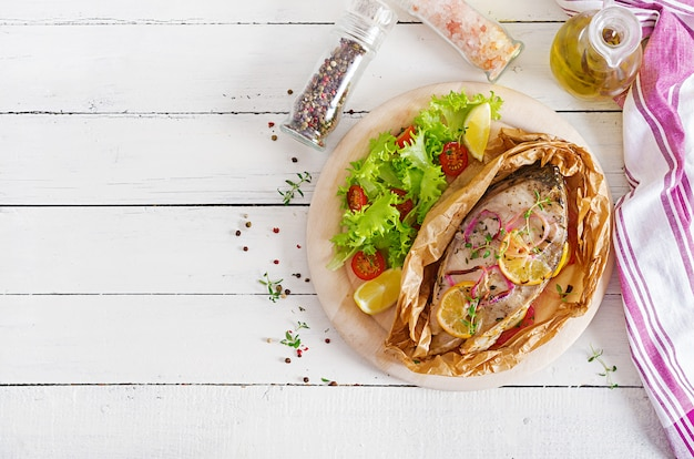 Steak de poisson blanc (carpe) cuit dans du papier sulfurisé avec des légumes.