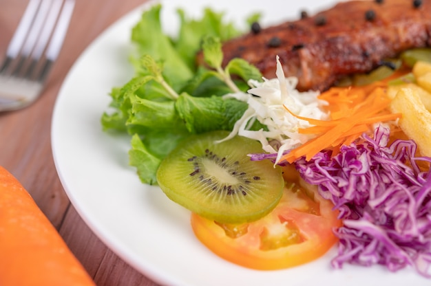 Steak de poisson avec frites, kiwi, laitue, carottes, tomates et chou dans un plat blanc.