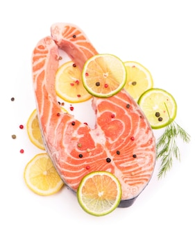 Steak de poisson rouge et citrons tranchés sur blanc