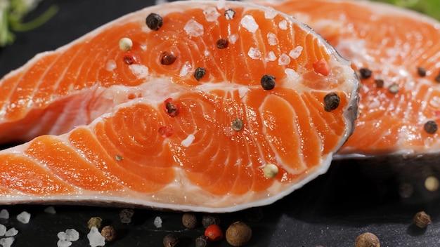 Steak de poisson rouge de truite crue de saumon aux herbes et au citron et à l'huile d'olive tourné sur ardoise