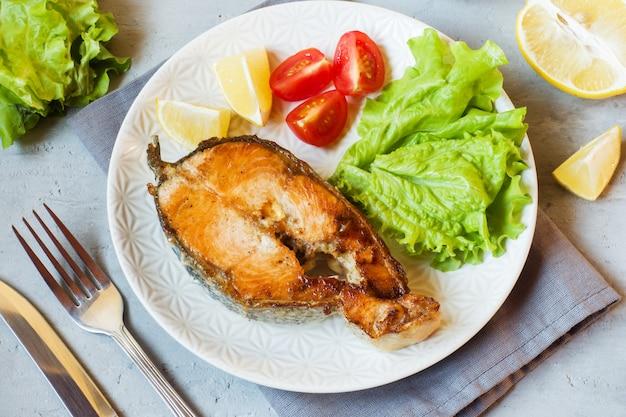 Steak de poisson saumon cuit au four sur une assiette avec des légumes frais.