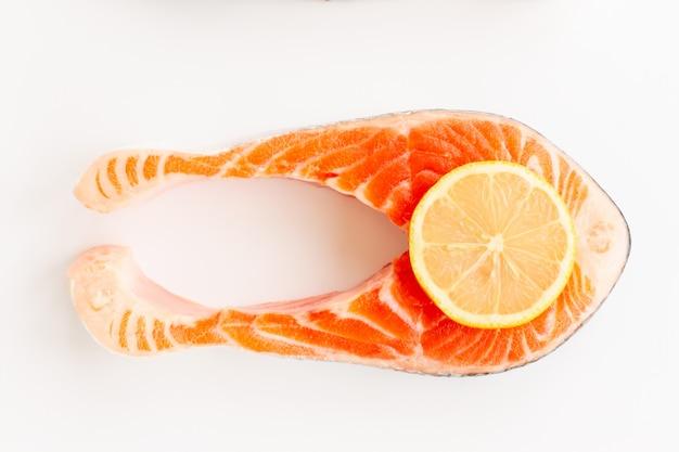 Steak de poisson de saumon rouge de mer fraîche avec une tranche de citron isolé sur fond blanc.
