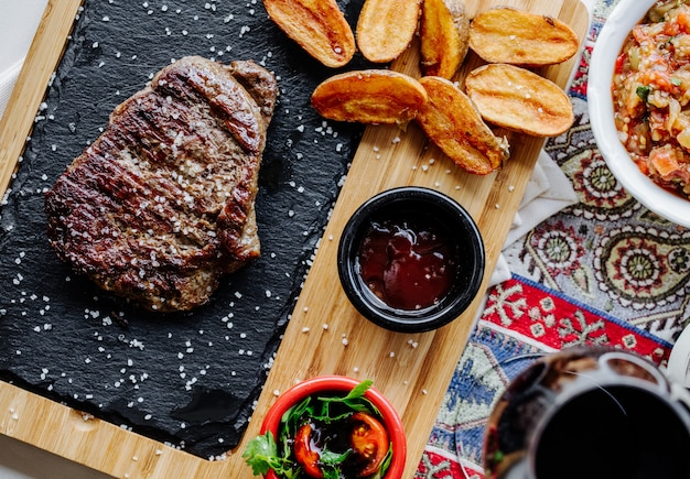 Steak et pommes de terre frites avec sauce barbecue et salade verte.
