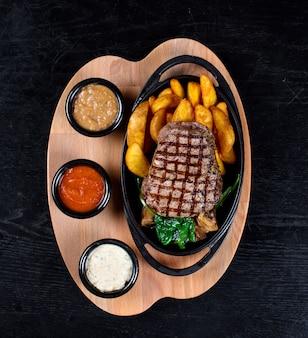 Steak avec pommes de terre frites et sauces