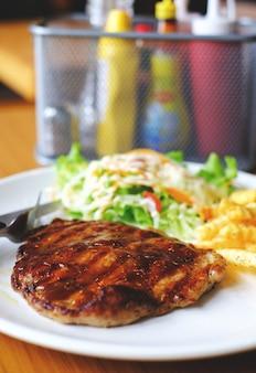 Steak de porc au porc avec salade et frites