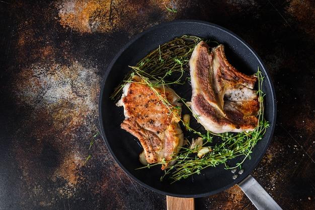 Steak de porc bio grillé aux herbes sur os dans une poêle à frire gril chaud avec de la fumée et de l'huile chaude juste du feu, vue de dessus os de cuisson avec assaisonnements fond métal rustique