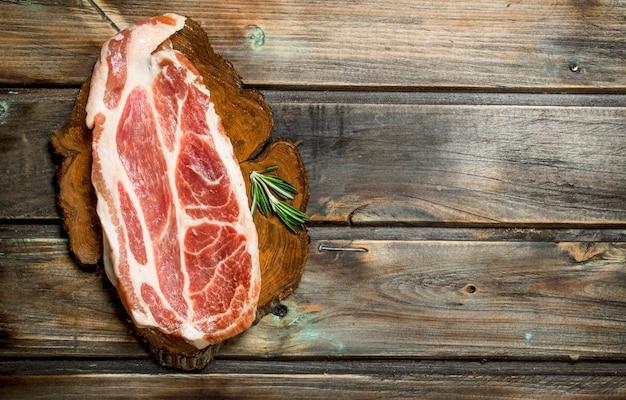 Steak de porc cru. sur un fond en bois.