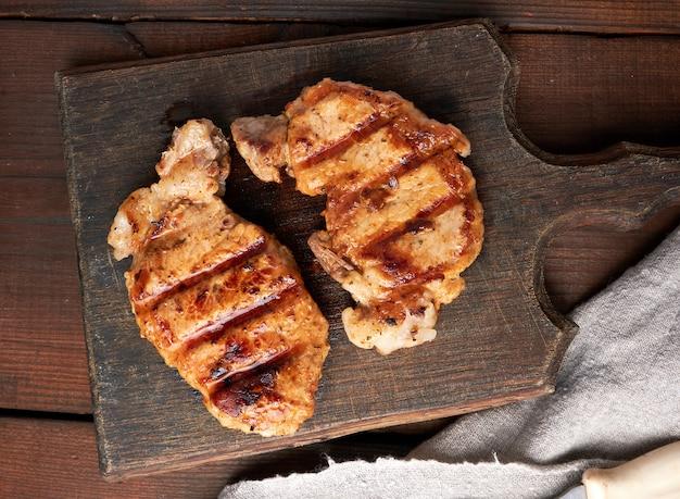 Steak de porc frit se trouve sur une planche de bois brune vintage