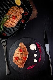 Steak de porc grillé sur assiette en ardoise.