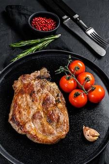 Steak de porc grillé aux tomates. fond noir. vue de dessus
