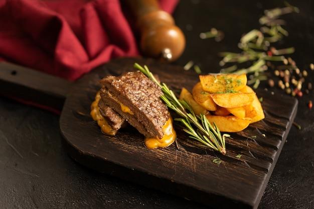 Steak de porc grillé chaud au romarin, pommes de terre au four et sauce au fromage. un plat chaud de viande et de pommes de terre sur une planche à découper sombre.
