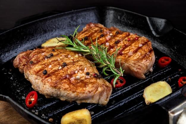 Steak de porc grillé dans une poêle avec du romarin, du piment rouge et du gingembre sur une planche de bois.