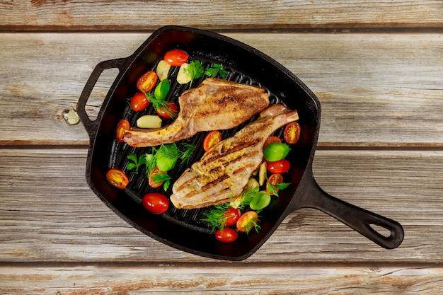 Steak de porc grillé dans une poêle en fer sur une surface en bois