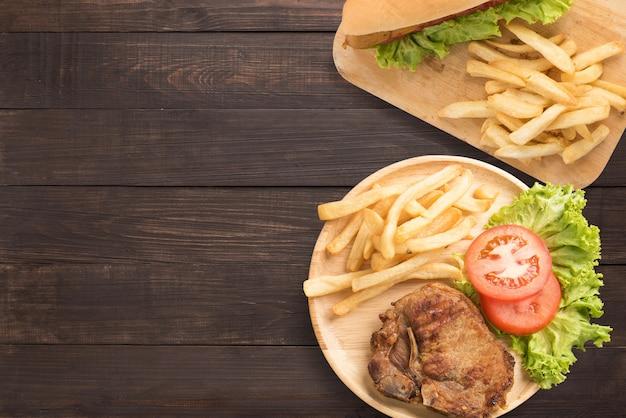 Steak de porc grillé et hot-dogs sur le fond en bois. copyspace pour votre texte