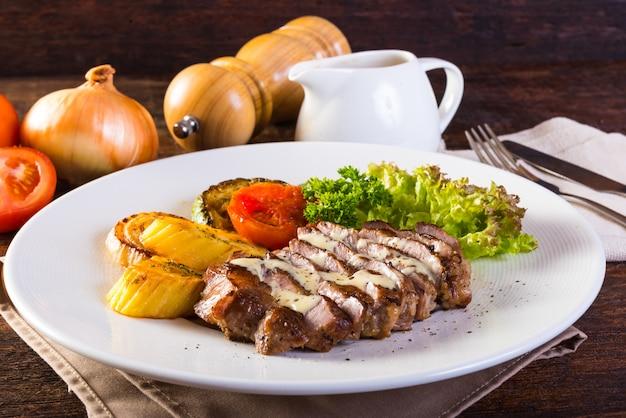 Steak de porc grillé, pommes de terre au four et salade de légumes sur une table en bois.