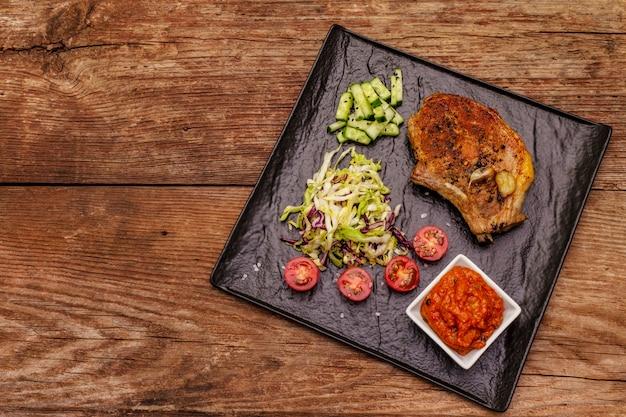 Steak de porc grillé avec sauce tomate et salade de chou