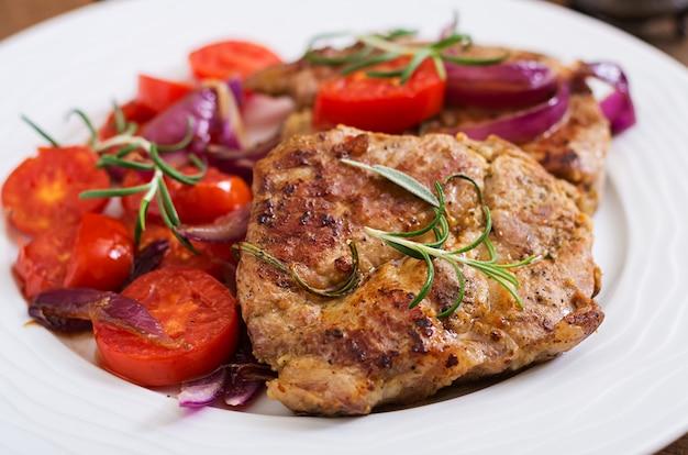 Steak de porc juteux au romarin et tomates sur une plaque blanche