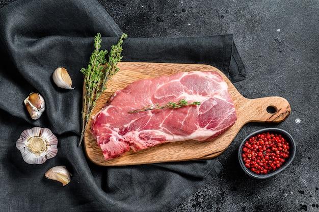 Steak de porc en marbre brut sur une planche à découper en bois. viande biologique. fond noir.