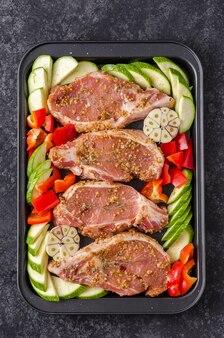 Steak de porc non cuit avec poivrons et courgettes sur une plaque à pâtisserie pour rôtir