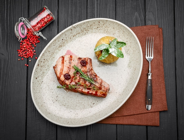 Steak de porc à l'os avec sauce cerise et gingembre avec ingrédients sur un sac en désordre