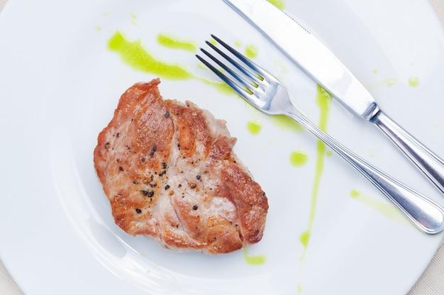 Steak de porc sur une plaque blanche avec une fourchette et un couteau. vue de dessus