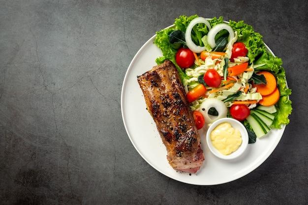 Steak de porc rôti et légumes sur assiette.