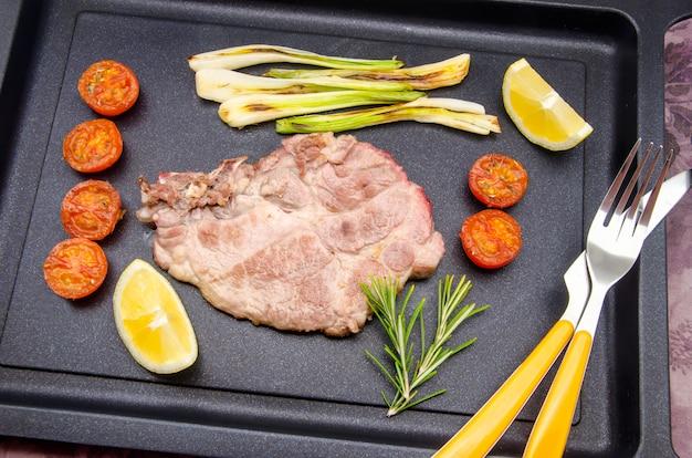 Steak de porc rôti avec tomates et légumes