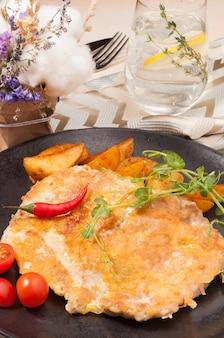 Steak de porc savoureux dans un manteau de fromage avec des tranches de pommes de terre