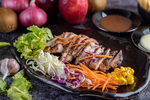 Steak de porc tranché avec du pain, des carottes, du chou-fleur, de la laitue et du maïs sur une plaque noire.