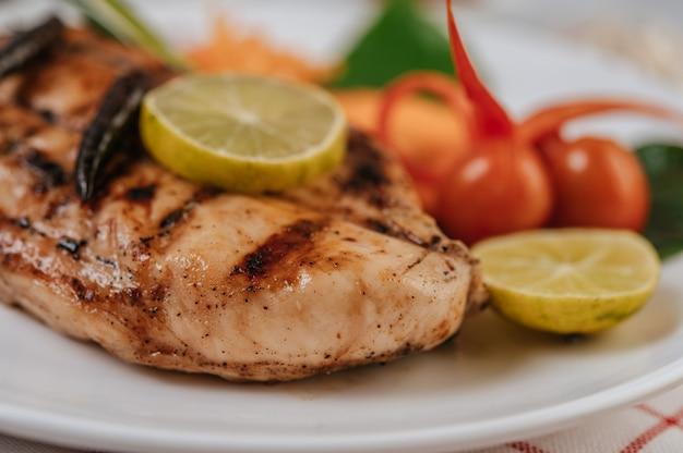 Steak de poulet au citron, tomate, chili et carotte sur plaque blanche.