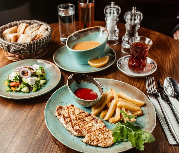 Steak de poulet avec frites et ketchup servi avec soupe et salade de légumes