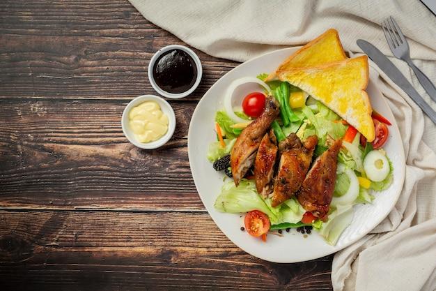 Steak de poulet grillé et légumes sur fond de bois foncé