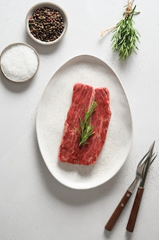 Steak de ribeye cru au romarin sur blanc.