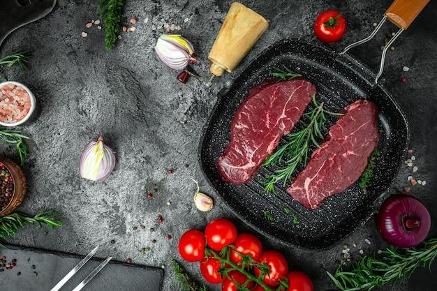 Steak de rumsteck cru ou haut de surlonge steak de viande de boeuf sur une poêle à griller sur fond noir. vue de dessus.