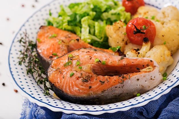 Steak de saumon au four avec chou-fleur, tomates et fines herbes. nutrition adéquat.