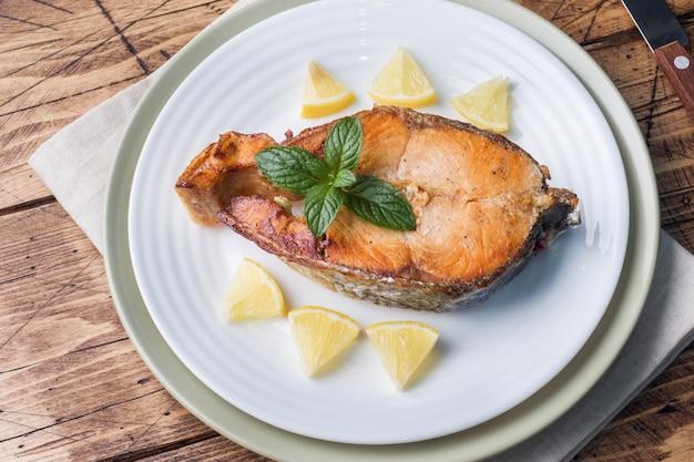 Steak de saumon au poisson sur une plaque au citron. table en bois.