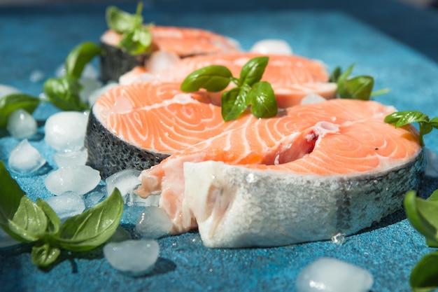 Steak de saumon cru et frais sur un fond bleu pierre et basilic. poisson rouge saumon cru.
