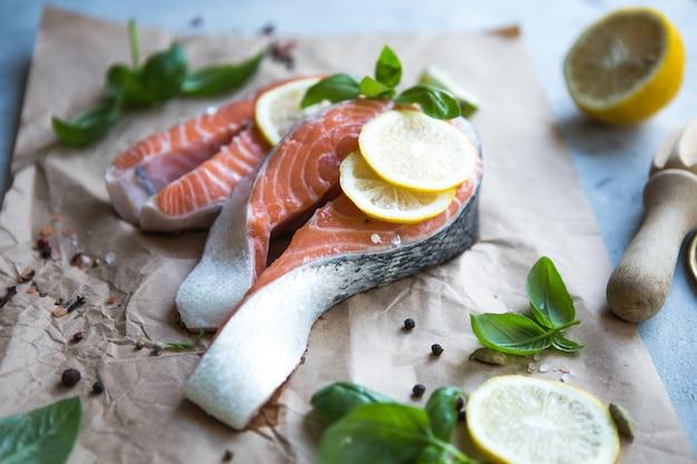 Steak de saumon cru et frais sur une pierre et du basilic, une tranche de citron autour. poisson rouge saumon cru.