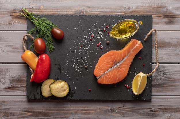 Steak de saumon cru sur une planche sombre près de légumes cuits au four tomates citron vert huile d'olive dans une boîte d'huile saine