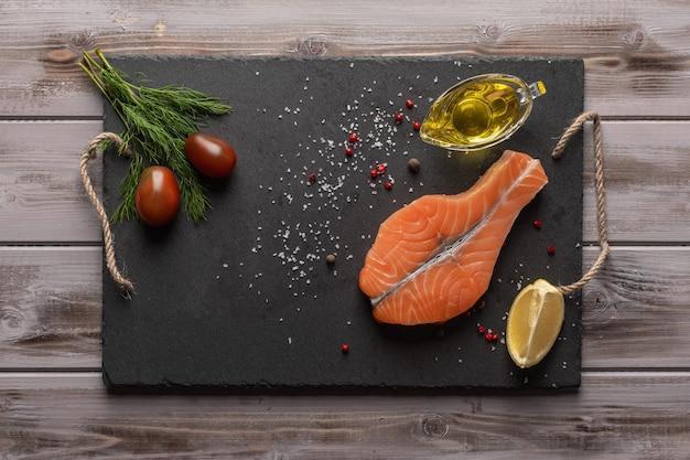 Steak de saumon cru sur une planche sombre près de tomates citron huile d'olive dans une huile peut vue de dessus des aliments sains