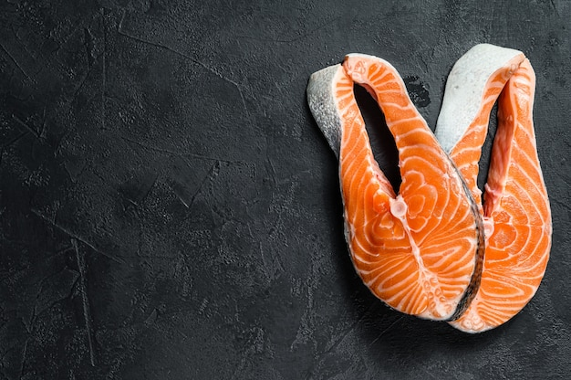 Steak de saumon cru. poissons de l'atlantique. fond noir. vue de dessus. espace pour le texte