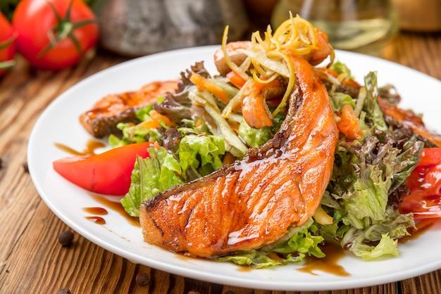 Steak de saumon dans un plat blanc avec des légumes
