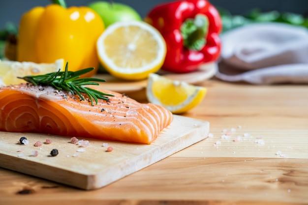 Steak de saumon frais aux herbes, citron et ingrédients pour la cuisson dans la cuisine