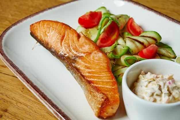 Steak de saumon juteux sur une plaque blanche avec garniture de tomates cerises et de concombre. table en bois. gros plan sur les délicieux fruits de mer du restaurant