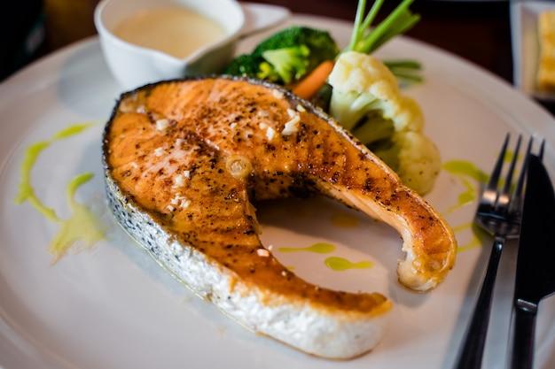 Steak de saumon sur la plaque blanche