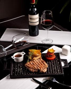 Steak servi avec pommes de terre, sauce aux légumes grillés et vin